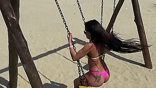 Playful babe swings outdoor at the beach